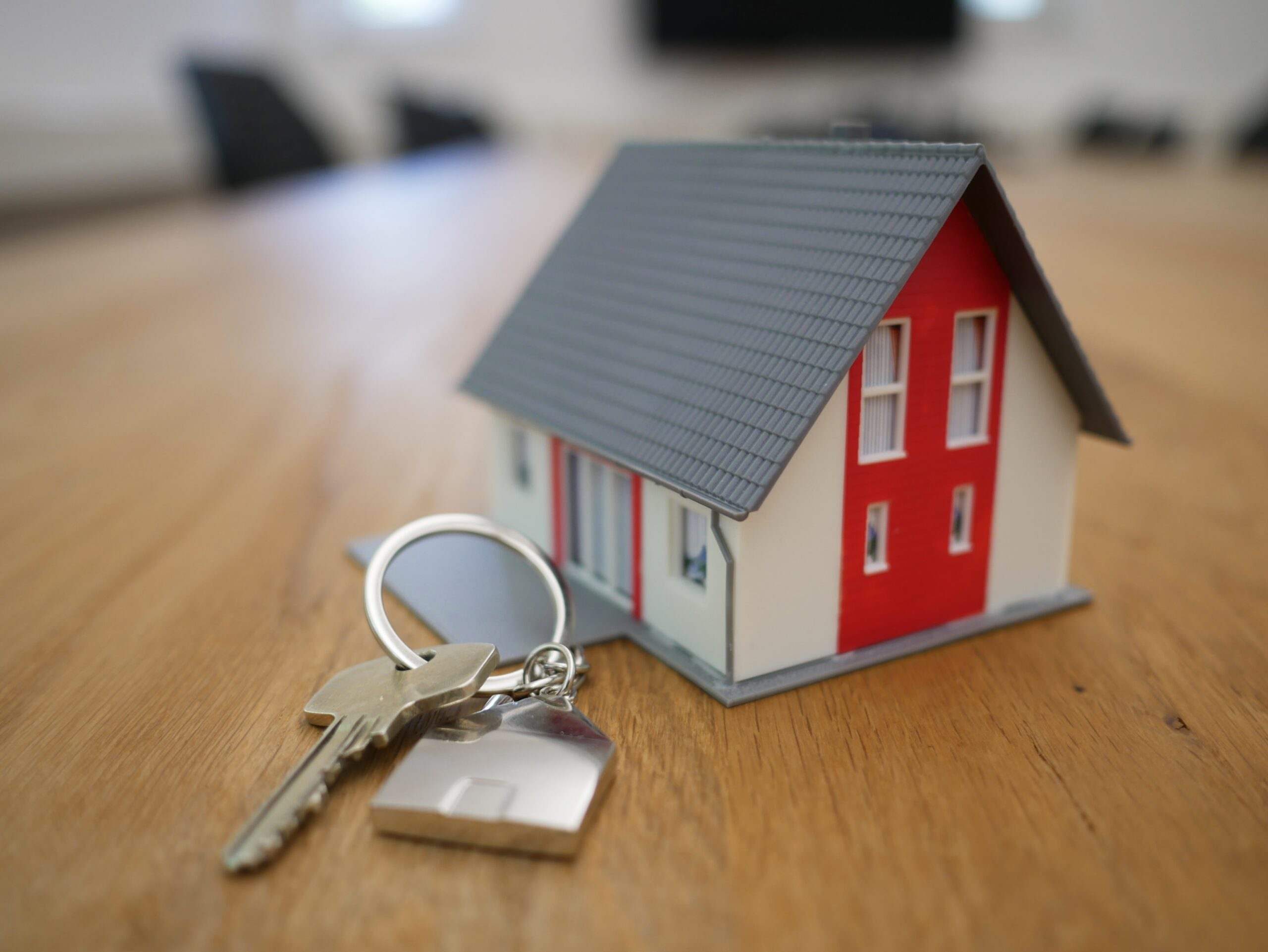 Set of Keys on a table with a model house attached