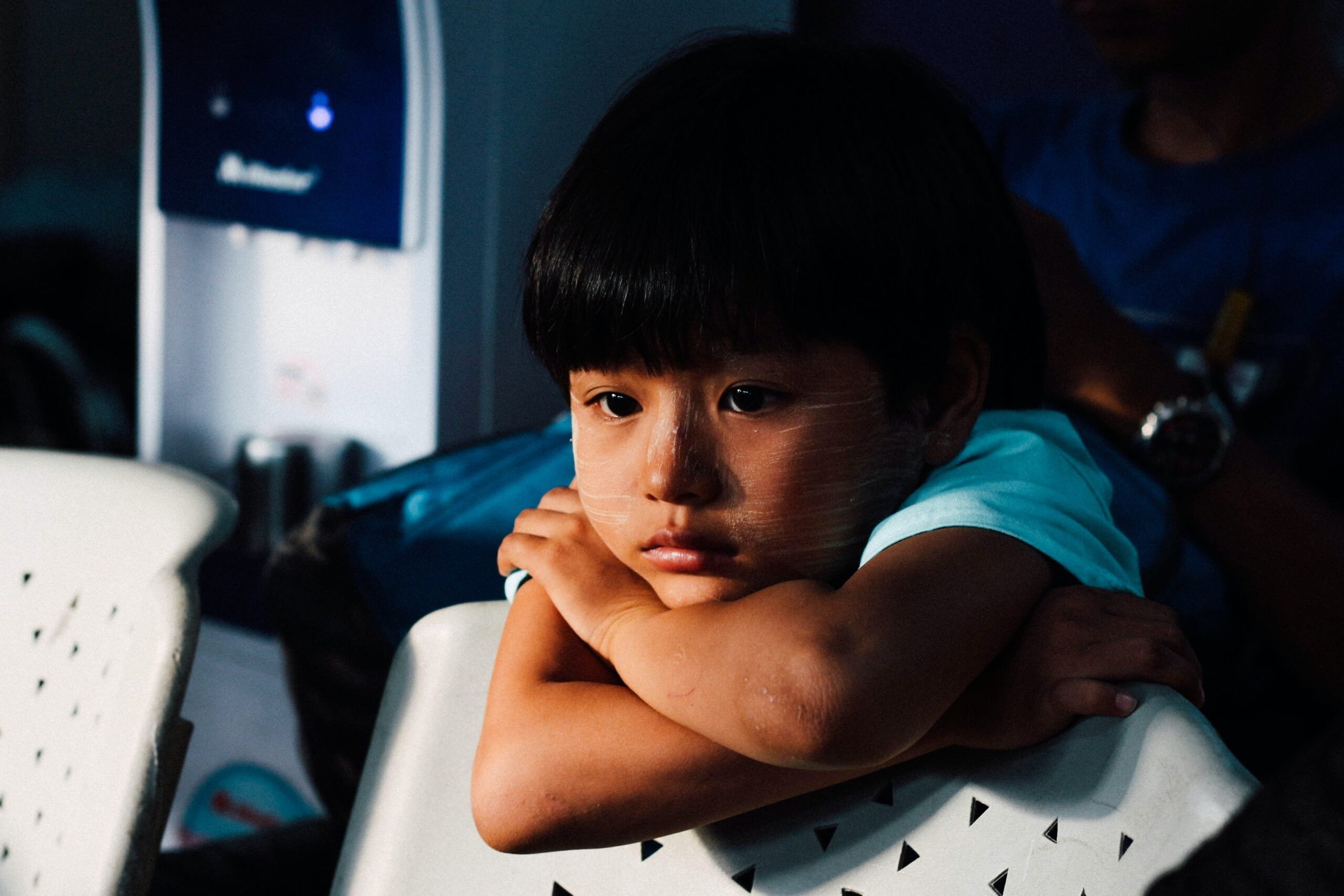 sad child leaning on a chair