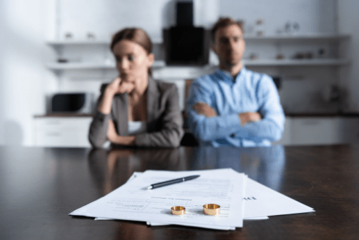 Man and woman sat a a desk with a contract on with rings and a pen on top