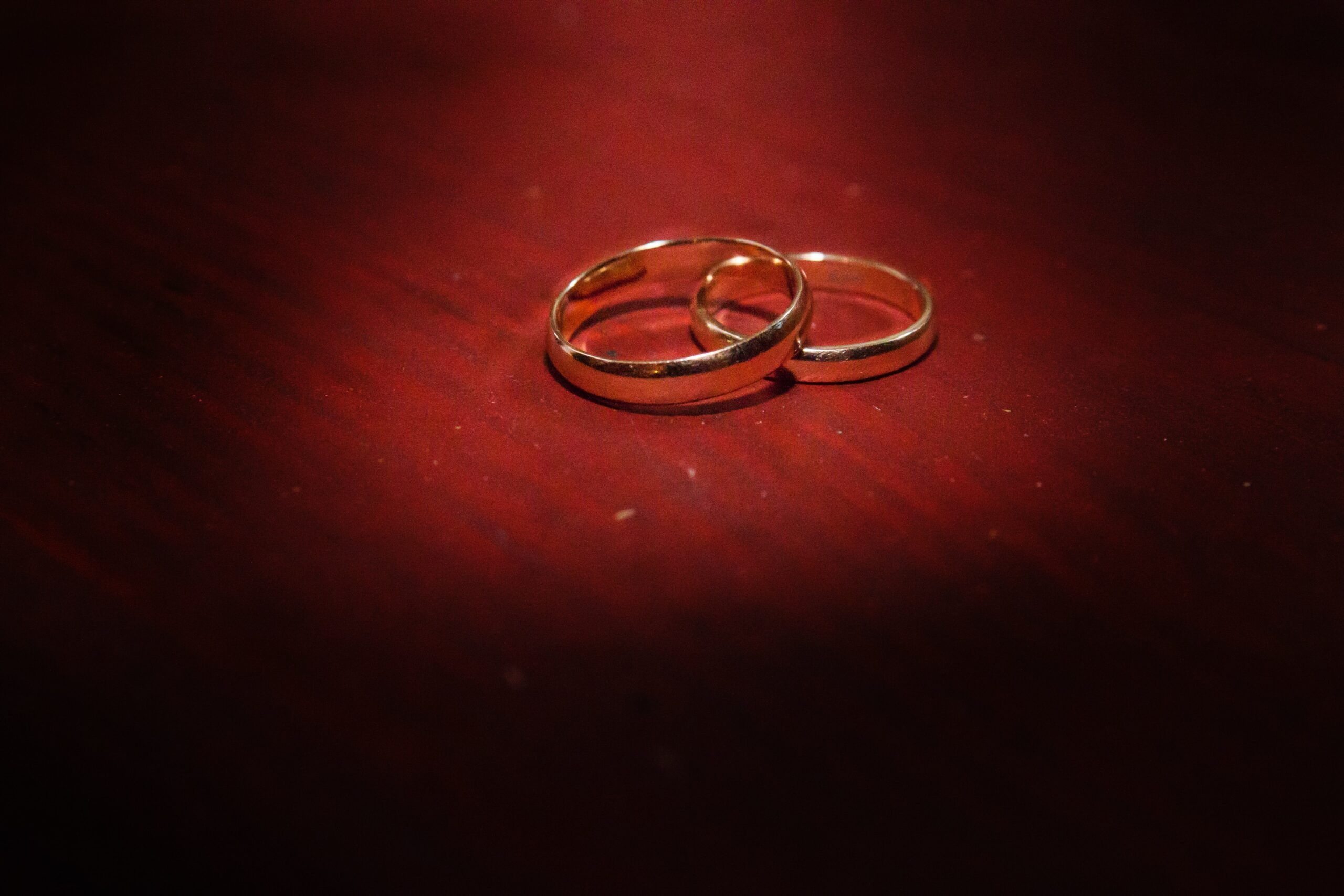 pair of gold wedding rings on red background